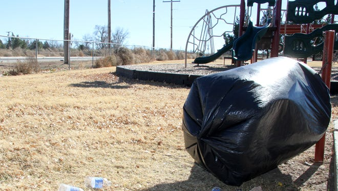 An overturned trash can and inverted bag blow in the wind at Cherry Lane Park north of Carlsbad.