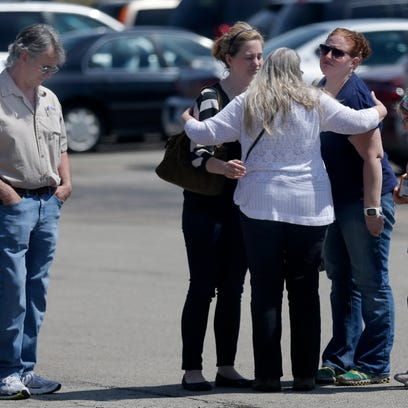 Mourners hug in the parking lot following a prayer service for victims at Calvary Bible Church on May 4, 2015 in Neenah, Wis. A shooting spree that resulted in four fatalities and one person injured occurred on the Fox Cities Trestle Trail bridge in Menasha Sunday night May 3, 2015 in Menasha.