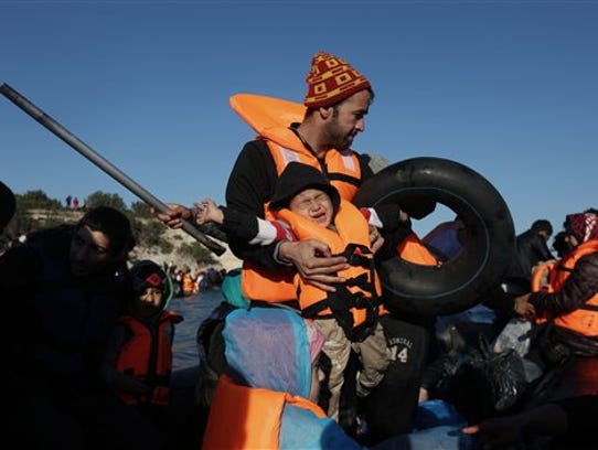 A child cries as migrants travel by dinghy to the Greek