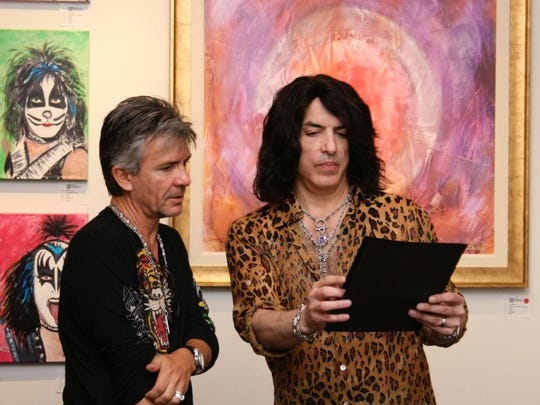 Gallery director Gerard Marti looks over a print that was created by Paul Stanley of Kiss.