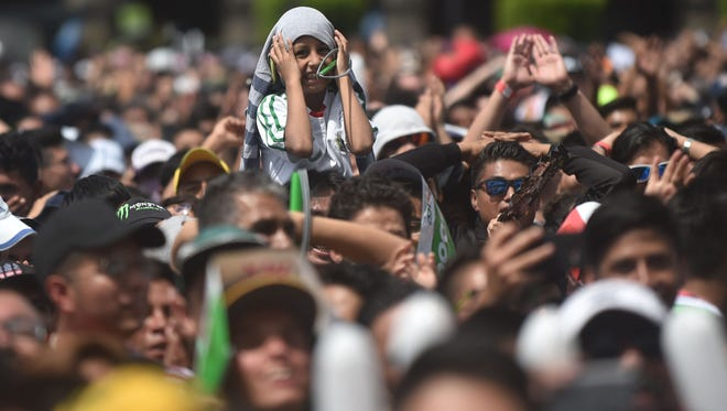 Fans of Mexico cheer for their team during the World Cup match against Germany, at a public event at Zocalo Square in Mexico City.