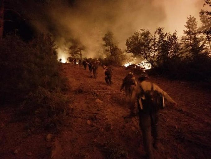 Firefighters hike toward heavy smoke from the Goodwin