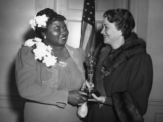 Hattie McDaniel poses with her historic Oscar and Oscar-presenter Fay Bainter during the 12th annual Academy Awards in 1940.
