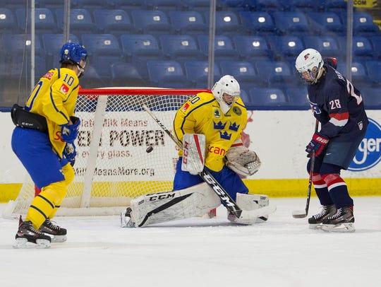 Team USA forward Joel Farabee (28) puts pressure on