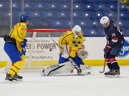 "Team USA forward Joel Farabee (28) puts pressure on Sweden goaie Jesper Eliasson while Adam Ginning (10) closes in. Farabee had an assist and played a strong game as a net-front presence on the power play, said U.S. head coach Seth Appert. ""He wins puck battles, he keeps plays alive, and he allows goals to happen."""
