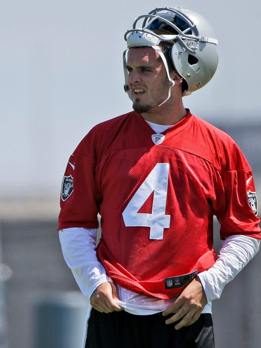 FILE - In this May 16, 2014, file photo, Oakland Raiders quarterback Derek Carr takes a break from drills during the team's NFL football rookie camp in Alameda, Calif.  Twelve years after his brother David started the season opener as a rookie quarterback in Houston, Derek Carr will get the nod for the Raiders. (AP Photo/Marcio Jose Sanchez, File)