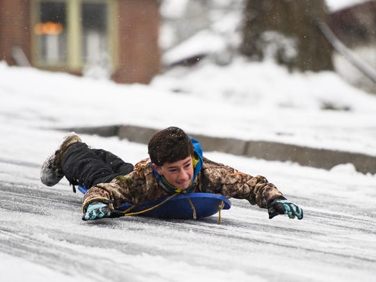 Charlie Kappel, 14, sleds down Townes Street in the North Main neighborhood on Wednesday, Jan. 17, 2018.
