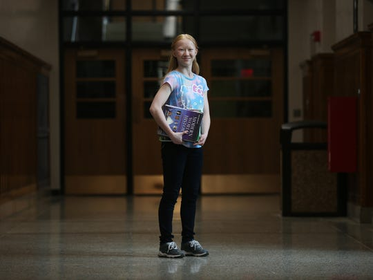 BaiYu Fisher, a freshman at Roosevelt High School, stands in a hallway of the school on Monday, April 10, 2017, in Des Moines. Fisher, adopted from China at the age of two, has albinism, a condition that would have kept her from going to school in her home country.
