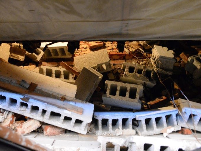 Fallen cinder blocks and bricks are pictured after the partial collapse of interior walls between two businesses in the 700 block of Landis Avenue on Friday, August 15, 2014.  Staff photo/Charles J. Olson
