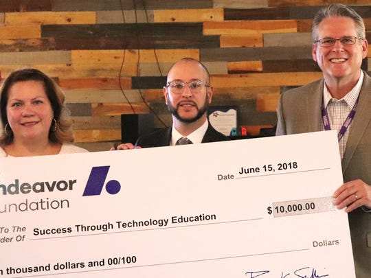 Joseph Sapien, executive director, Success Through Technology Education Foundation, center, gets a check from VJ Smith, government and public affairs manager for Andeavor, along with Anna Alemán, development director for the Paso del Norte Foundation, at a June 15 ceremony.