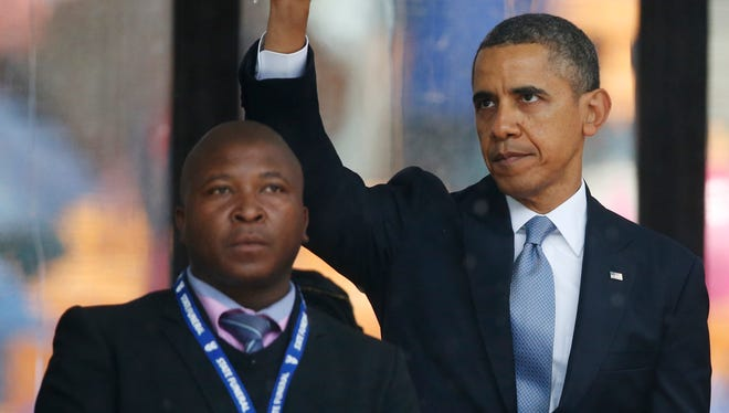 President Obama waves standing next to the sign language interpreter afters speaking at the service for former South African president Nelson Mandela in Johannesburg on Dec. 10.