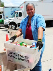 During the 22nd annual National Letter Carrier Food Drive on May 10, service volunteers helped letter carriers collect food left by mailboxes on various routes.