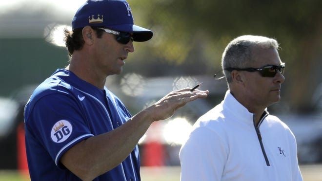 Kansas City Royals manager Mike Matheny, left, talks with general manager Dayton Moore during spring training baseball practice Wednesday, Feb. 12, 2020, in Surprise, Ariz.