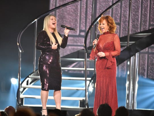 Kelly Clarkson, left, and host Reba McEntire perform