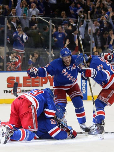 The Rangers pile on top of Carl Hagelin, who scored