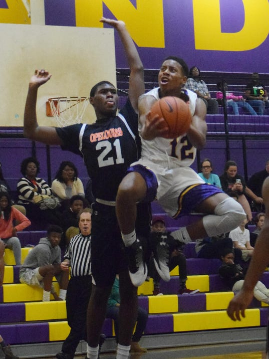ASH's Jordon Hunt (12) goes for two agianst Opelousas' Dashawn Foster (21, left), Tuesday.