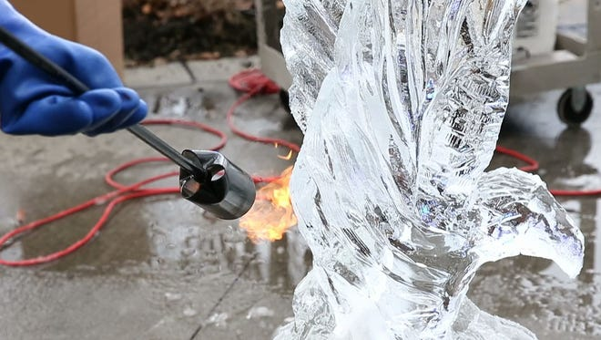 Fire is applied to an eagle ice sculpture to make the ice transparent.
