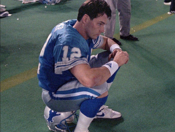 Lions QB Erik Kramer sits on his helemt and waits as