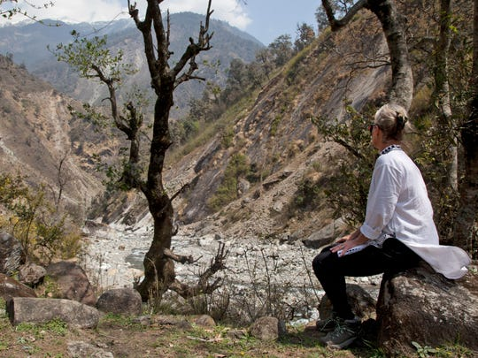 """In this March 26, 2017 photo, Elizabeth Brenner rests on a rock on the Milam Glacier Trail near the town of Munsiyari, in the mountains of north India. Brenner was on a """"pilgrimage"""" following the last footsteps of her son, Thomas Plotkin, a University of Iowa student who slipped and fell more than 300 feet down a steep gorge while on a study abroad trip to the mountains of India in September 2011. His body was never found. Hundreds of thousands of American students study abroad each year, but no one can say exactly how many are injured or die."""
