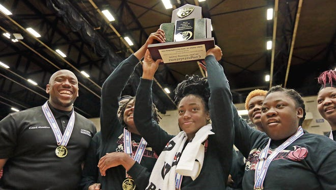 Madison County (1) Tamiera Mobley holds the championship trophy aloft surrounded by her senior teammates after they defeated Trenton 73-58 to win the FHSAA 1A Girls State Championship Basketball Game at the Lakeland Center in Lakeland, Florida February 17, 2016. The Ledger/Pierre DuCharme
