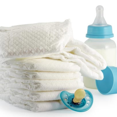 A stack of baby diapers bottle and a pacifier