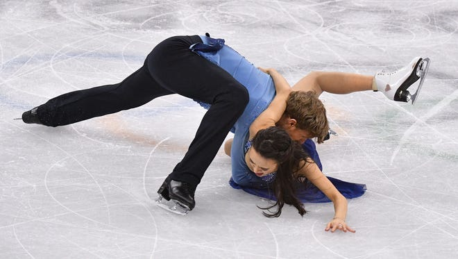 Madison Chock and Evan Bates (USA) fall to the ice as they perform in ice dancing.