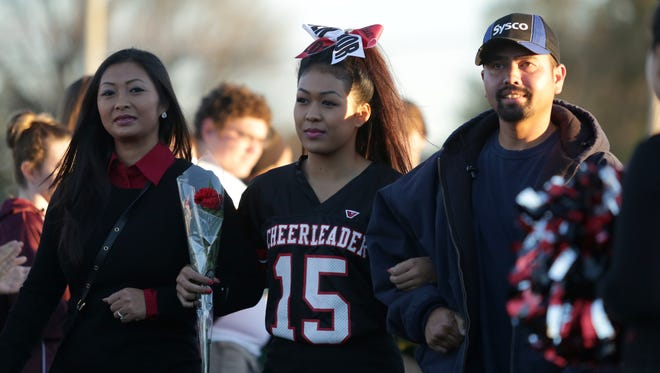 Des Moines East senior Asia Bell is escorted by her parents, Sokha Mom and Boundi Mom on senior night at Williams Metro Stadium in Des Moines.