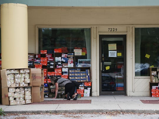 A woman looks for a pair of shoes during the Fitness Sports moving sale on Thursday at the Apple Valley shopping center in Windsor Heights. The store will open at a new location in Clive on Oct. 5.