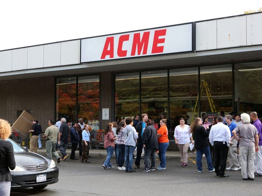 Workers stand outside the ACME supermarket during an