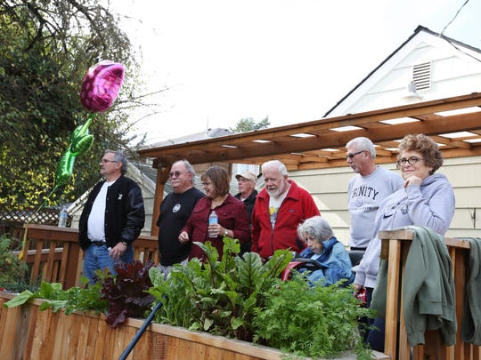 Connie Lee, center, and neighbors watch as a crew from DeSantis Landscapes helps the Englewood neighborhood finish its outdoor home makeover for her Saturday, Oct. 24, 2015, in Salem, Ore. Lee has a severe case of rheumatoid arthritis. She uses a power mobility scooter to get around and is unable to tend to her neglected yard in northeast Salem.