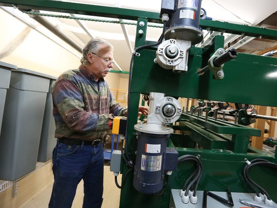 Wayne Doolin shows how a spinning machine works Wednesday, Dec. 16, at Skyline Fiber Mill in Salem, Ore. Wayne and his wife, Eileen, process natural fibers, such as wool and alpaca.