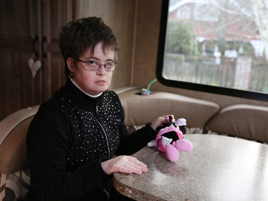 Khrizma Kuhn, 33, who has numerous disabilities, including Down Syndrome and autism, sits in her family's motor home on Wednesday, Jan. 13, 2016, at their home in Woodburn, Ore. Her parents, Renee and Gary Kuhn, purchased the motor home to travel with Khrizma. She also suffers from severe bladder and bowel incontinence, so even short trips can be an issue. The motor home is their solution to this problem.