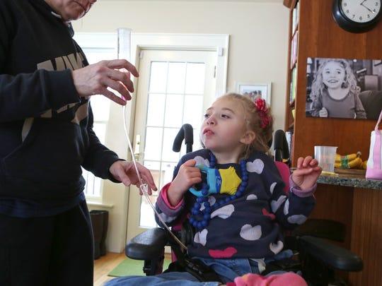 Nurse Terriann Federighi gives Morgan Jones, 5, her medication.