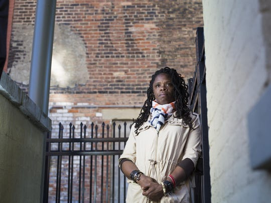 """Iris Roley is photographed in Over-the-Rhine near the spot where Timothy Thomas died 15 years ago. """"RIP,"""" which was written there soon after Thomas' death, is still visible on the brick wall behind her."""