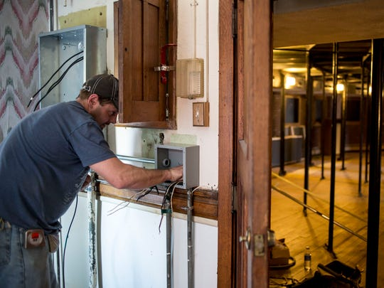 Electrician Chad Whitman works on upgrading the electric service as part of $387,000 in repair work Friday, April 15, 2016 at the Port Huron Museum.