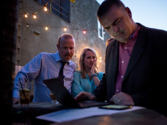 Superintendent James Cain waits in anticipation for results with his wife, Angie Cain, as Theo Kerhoulas, executive director of innovation, uses a laptop during a gathering in support of the Port Huron Schools bond proposals Tuesday, May 3, 2016 at Casey's Pizza and Subs in Port Huron.