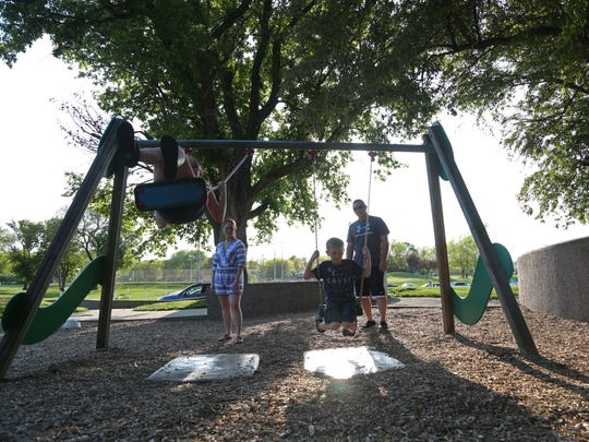 Jessica and Jacob Hoenicke push their children Dezi, 12, and Cayden, 9, on swings at Walker Johnston Park in Urbandale.