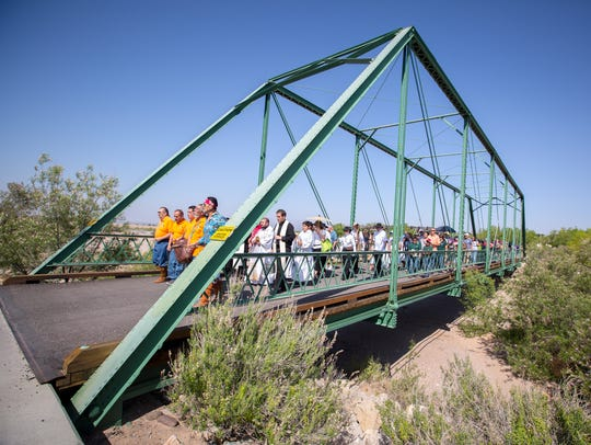 A procession crosses a bridge at the New Mexico Farm