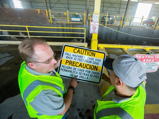 South Central Solid Waste Authority regulatory compliance specialist Steve Mauer, left, and transfer station attendant Arturo Ramos, right, discuss sign improvements on Friday May, 13, 2016, that are being made at the facility after working with OSHA to ensure the workplace is safe.