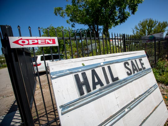 A sign advertising plants for sale damaged by Wednesday's hail storm is propped up outside of Guzman's Greenhouse on Avenida de Mesilla, May 19, 2016. An employee of Guzman's estimates that the store lost half its stock, mostly flowering and bedding plants as a result of the storm.