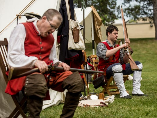 Alex Fuller, of Ypsilanti, right, cleans his Brown Bess musket next to James Cain, of Grand Rapids, during the Feast of the Ste. Claire Saturday, May 28, 2016 at Pine Grove Park in Port Huron.