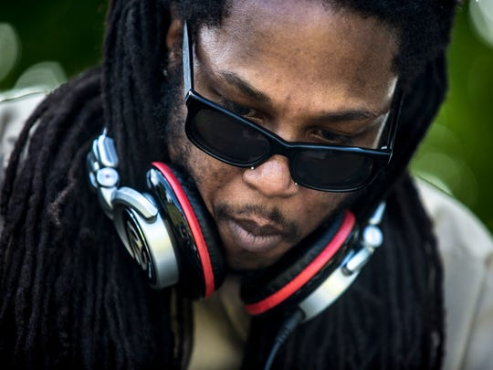 Zenas Jackson of Monkey Blood wears headphones and looks down at his turntables as he performs during Pine Groove electronic music festival Saturday, June 4, 2016 at Pine Grove Park in Port Huron.