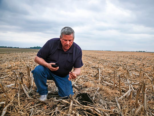 Former Iowa Secretary of Agriculture Bill Northey pulls up a soybean that was planted into the remains of last year's corn crop at his farm in Spirit Lake in 2016.