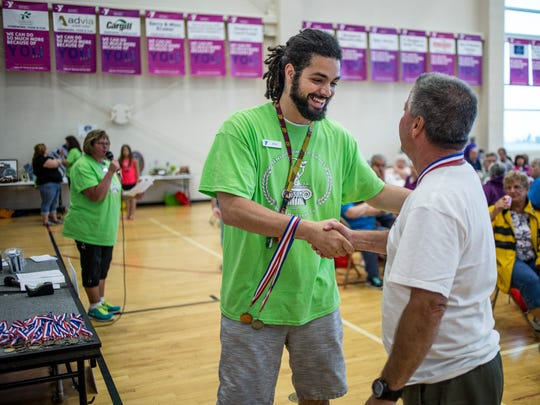 Josh Chapman shakes hands with Tim Hudy, of Fort Gratiot, after handing him a medal for the half-mile walk during the Senior Olympics Thursday, June 16, 2016 at the YMCA of the Blue Water Area in Port Huron.