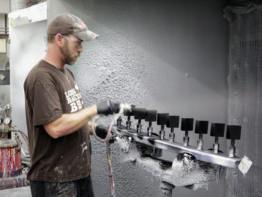 AJS and Associates employee Mike Tolbert paints a line of tap handles in the paint area at the firm Wednesday June 15, 2016 in Random Lake.