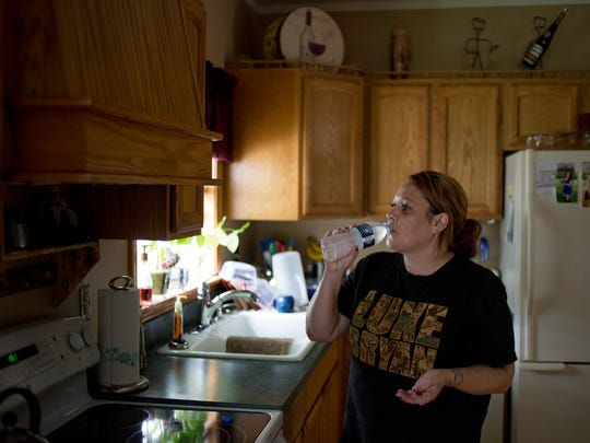 Aimee Dort takes her afternoon pills Thursday, June 23, 2016 at her Kimball Township home. Dort said she takes at least 10 pills each day to treat her CRPS.