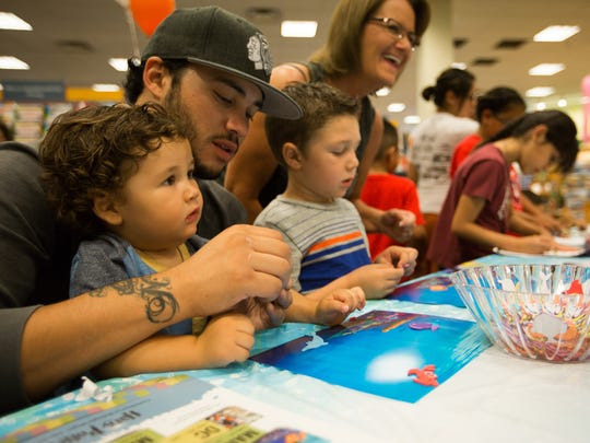 "Tony Buckman, left, joined with his sons Kaysen Buckman, 1, Kamden Buckman, 4, and grandmother Trish Buckman to create their own Dory-themed aquarium during Barnes & Noble's ""Get Pop-Cultured: Finding Dory"" event on Friday July 8, 2016."