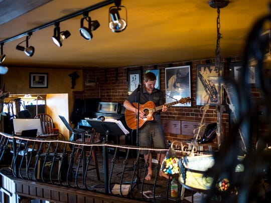Port Huron native Julian Ruck plays the guitar Tuesday, August 16, 2016 at The Raven Cafe in downtown Port Huron. Ruck is attempting to break the world record for a non-stop guitar performance,  and will attempt to continue to play until Sunday.