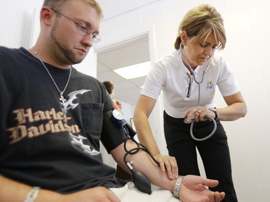 In this 2013 photo, Ervin Kegley of Morehead, Kentucky, a recovering addict, gets vital signs taken at Northern Kentucky's first Harm Reduction Clinic, a naloxone clinic in Falmouth.