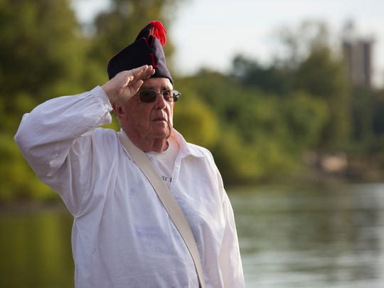 Hamp Williams salutes the American flag as other reenactors with the Lewis and Clark expedition take them down off the ships after they docked in Henderson, Ky., on Monday evening.